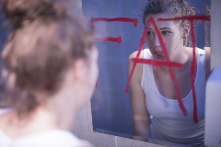 Fat red writing on mirror and teenage girl
