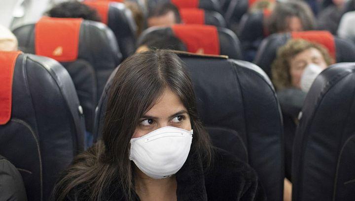 Una viajera con mascarilla a bordo de un avión.