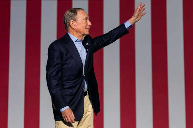 Democratic presidential candidate Mike Bloomberg waves to supporters as he arrives to his campaign rally...