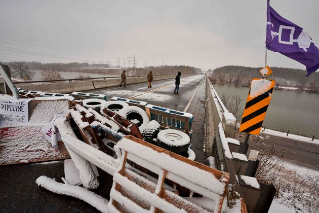 ファーストネーションズの抗議者は、オンタリオ州カレドニア近くの高速道路6のバリケードを通過する橋の上を歩きます。