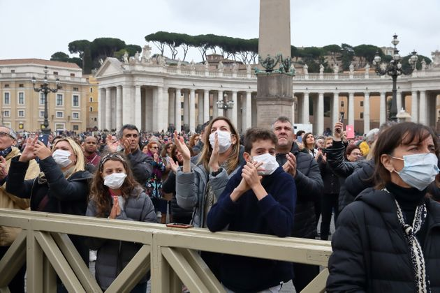 Pilgrims arrive in St. Peter's Square at the Vatican wearing masks to protect themselves from COVID-19...