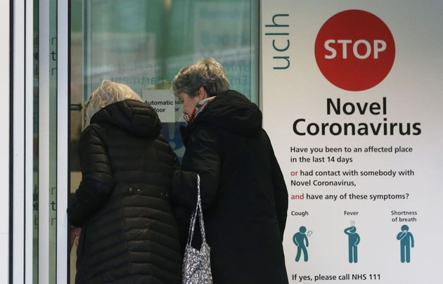 Two women walk past a sign providing guidance information about novel coronavirus in