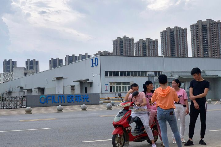In this photo taken Wednesday, June 5, 2019, neighborhood residents chat near the entrance to an OFLIM factory in Nanchang in