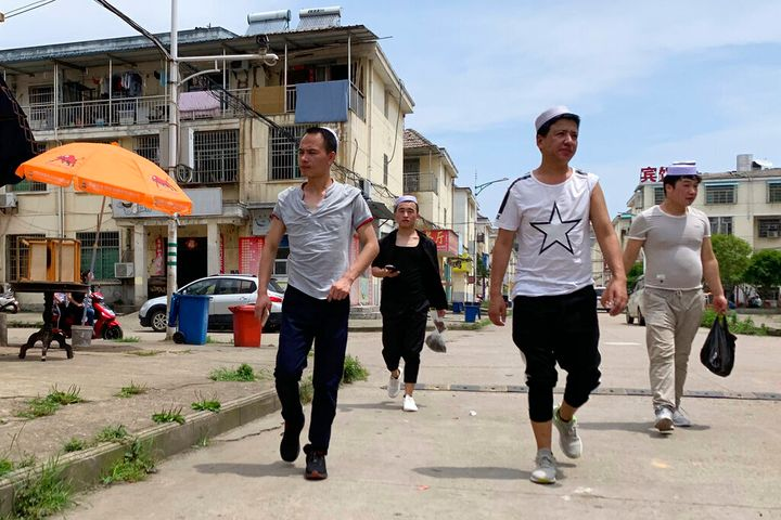 In this photo taken Wednesday, June 5, 2019, residents of the Hui Muslim ethnic minority walk in a neighborhood near an OFLIM