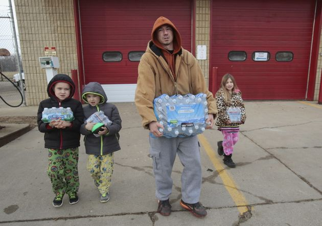 Flint resident Jerry Adkisson and his children carry water bottles from a fire