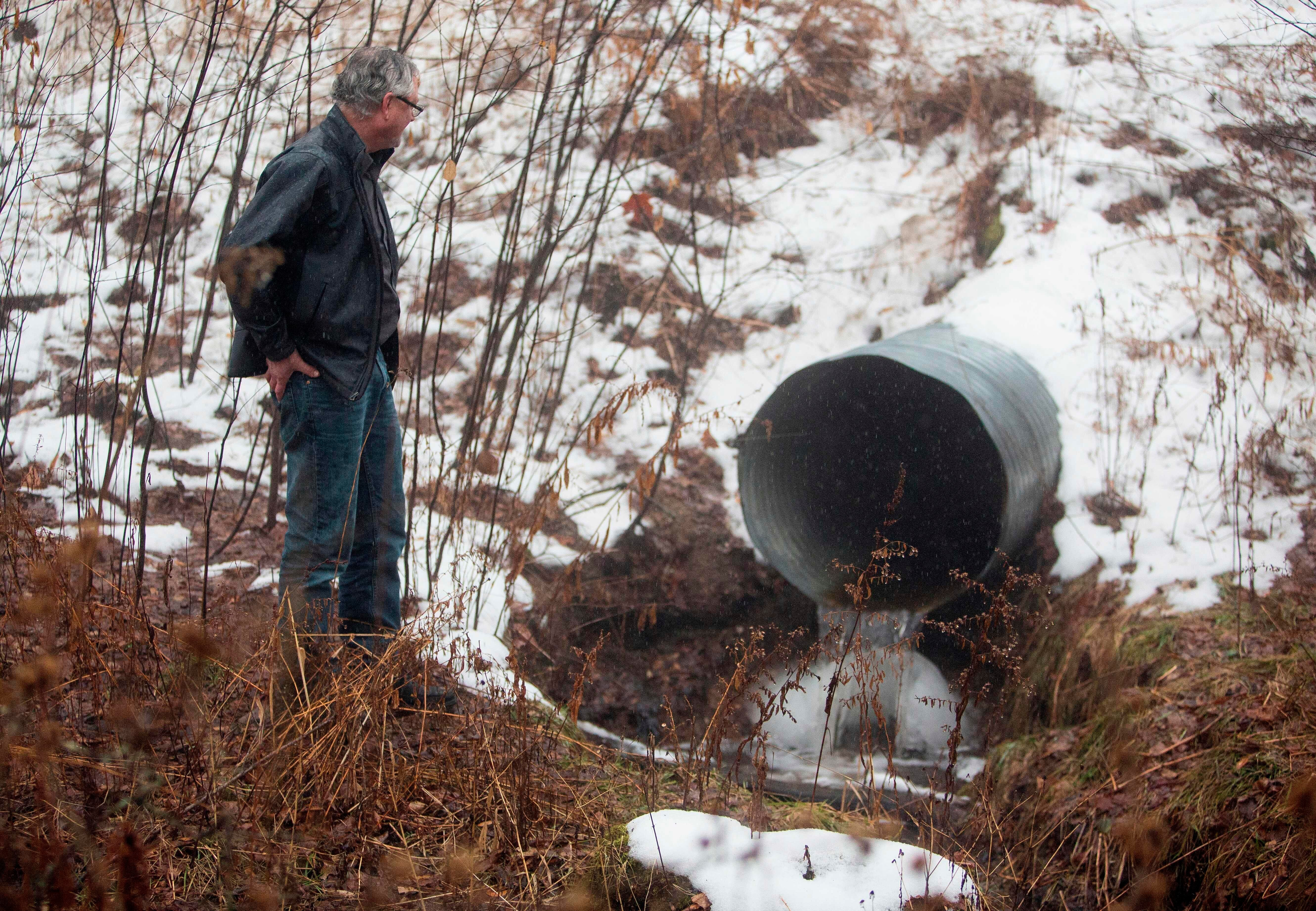 David Huff, chair of the zoning and planning commission for Osceola Township, stands before Chippewa Creek, shown flowing through a culvert where global food conglomerate Nestle is in a battle with critics in the tiny town over its water extraction.