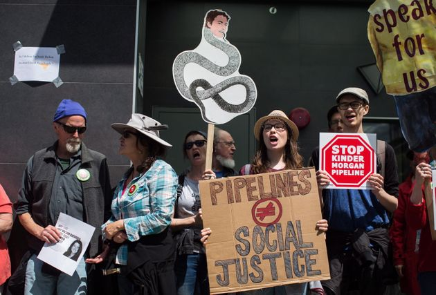 A woman holds a sign with a drawing of Prime Minister Justin Trudeau's face on a snake as protesters...