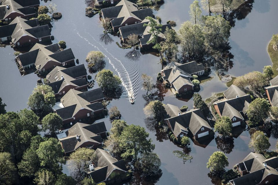 A boat makes it way past flooded property after HurricaneFlorence past through Wallace, in North...