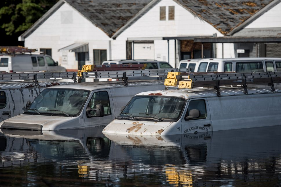 Vehicles are submerged vehicles at a Robeson County school parking lot on Oct. 12, 2016, in Lumberton, North Carolina.