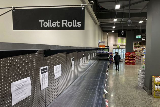 A shopper passes empty shelves usually stocked with toilet paper in a supermarket in Melbourne on March...