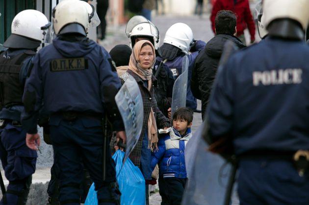 Refugiados miran hacia un cordón de policías