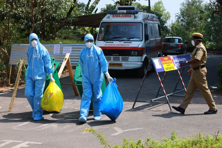 Health officials in full protective apparel carry medical waste out of an isolation ward of Ernakulam Medical College, where 12 suspected coronavirus patients were kept in quaratine, in Kochi on February 4, 2020.