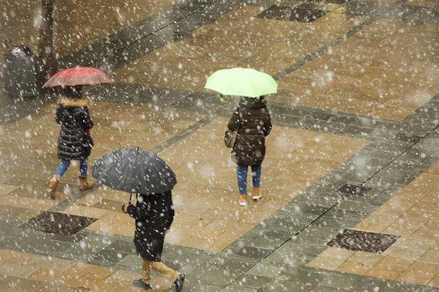 Varios transeúntes se protegen de la nieve en