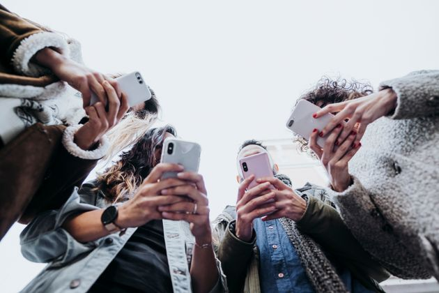 People are seen here using their smartphones in this stock photo. The federal government says wireless...