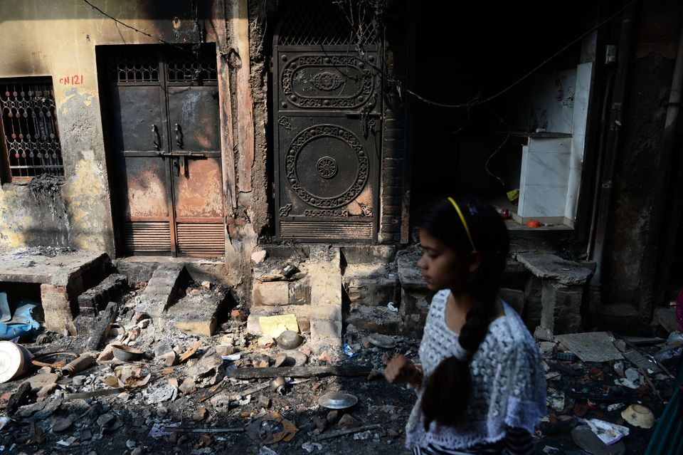 A resident walks past a burnt-out building on a residential area, in New Delhi on March 1,