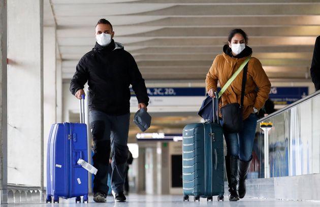Des voyageurs portant des masques de protection contre le coronavirus à l'aéroport de Roissy...