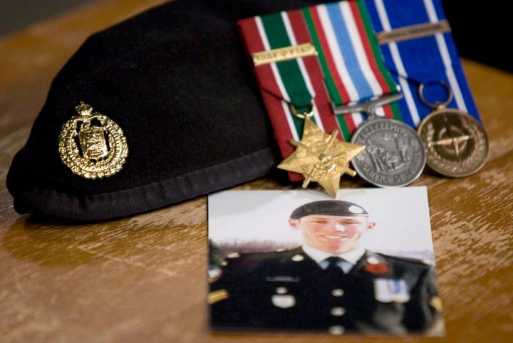 A photo of Cpl. Stuart Langridge is seen along with his beret and medals at a news conference on Parliament Hill on Oct. 28, 2010.
