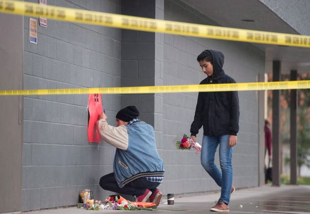 Young men arrive to lay flowers at a makeshift memorial outside Abbotsford Secondary School on Nov. 2, 2016.