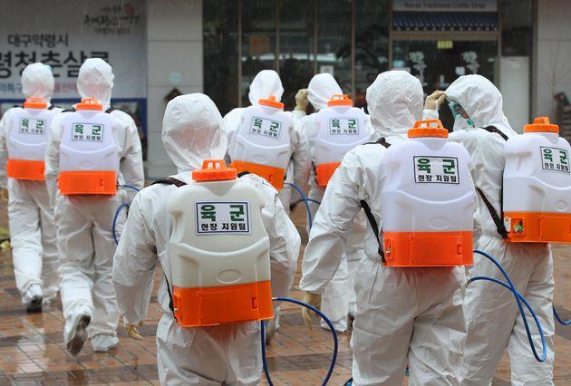 7일 오전 육군 제50사단 장병들이 신종 코로나바이러스 감염증(코로나19) 확산을 막기 위해 대구 중구 약령시 주변에서 방역을 하던 중 비가 내리자 실내 방역을 위해 이동하고