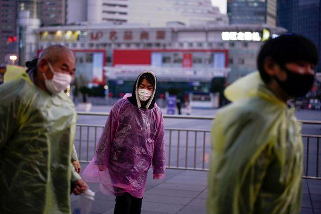 상하이 기차역 인근에서 비닐 비옷과 마스크로 '무장'한 시민들이 거리를 걷고 있다. 2020년