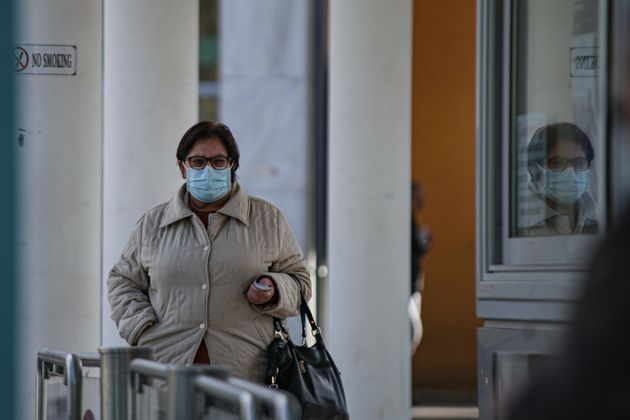 A woman wearing a protective face mask walks outside of the Hospital that the first Coronavirus case...