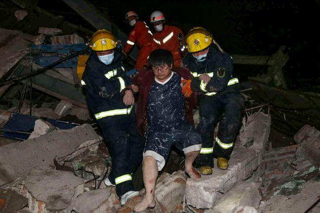 중국의 '신종 코로나' 수용 시설 매몰 현장에서 시민이 구조대원의 도움을 받아 빠져나오고
