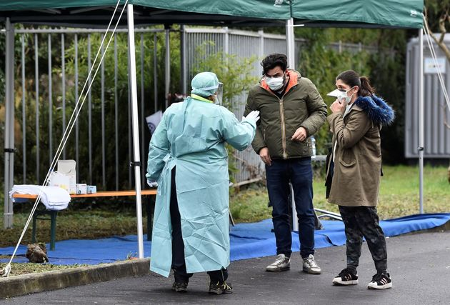 A medical worker wearing protective mask speaks to people at a medical checkpoint at the entrance of...