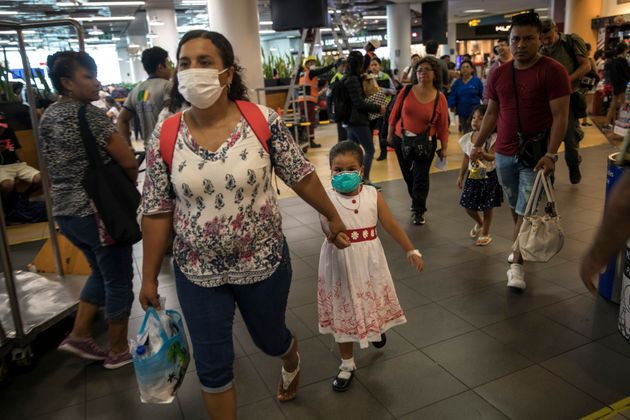 Wearing masks, passenger Gladys Ruiz Torres walks with her daughter Natali Oliva to the departure lounge...