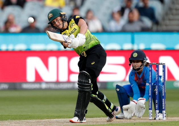 Australia's Alyssa Healy, left, drives the ball in front of IndiaÅfs Tanya Bhatia during the WomenÅfs...