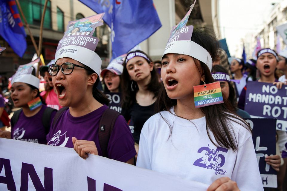 Women's rights activists shout slogans during a protest Manila,