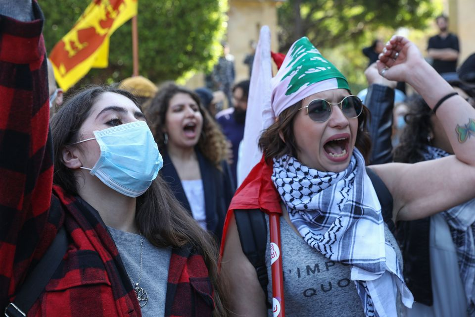 Lebanese women, including one wearing a protective mask due to coronavirus, gesture during a march in