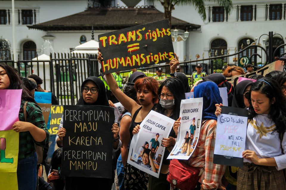 Protesters hold placards during a protest in Bandung,