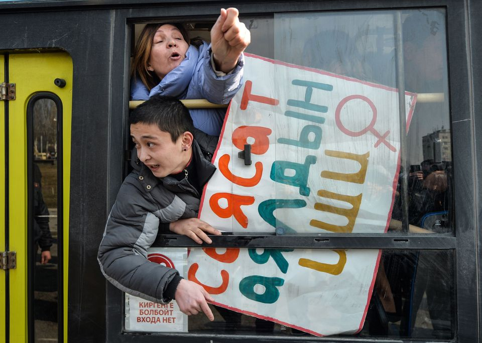 Women gesture from a police van after they were arrested while protesting against gender-based violence...