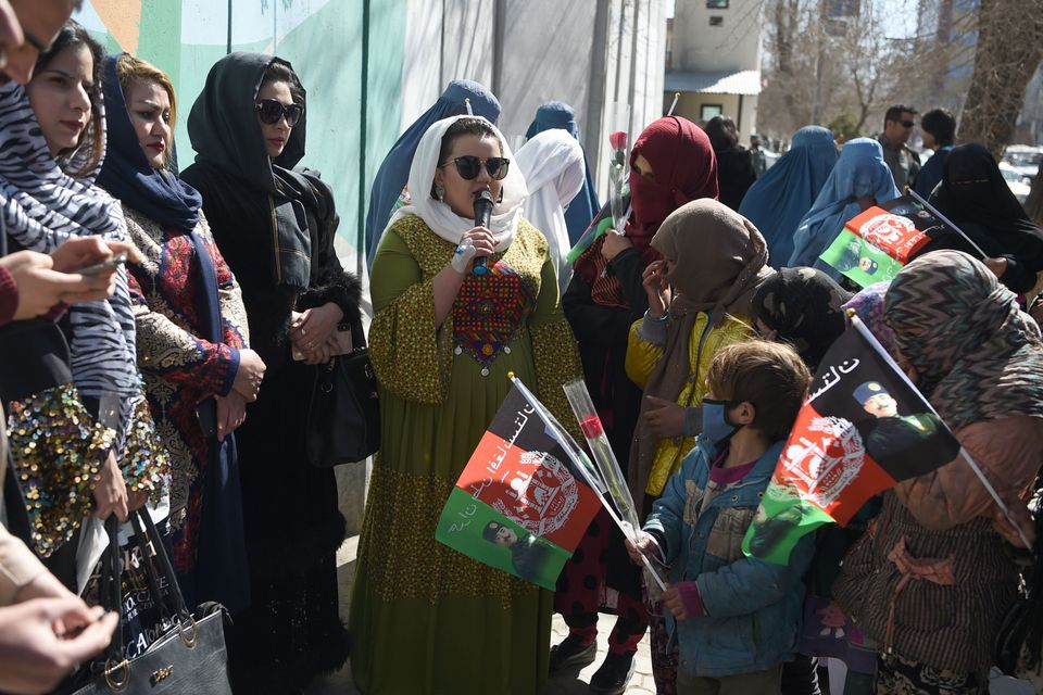 Afghan civil activists gather along a road in