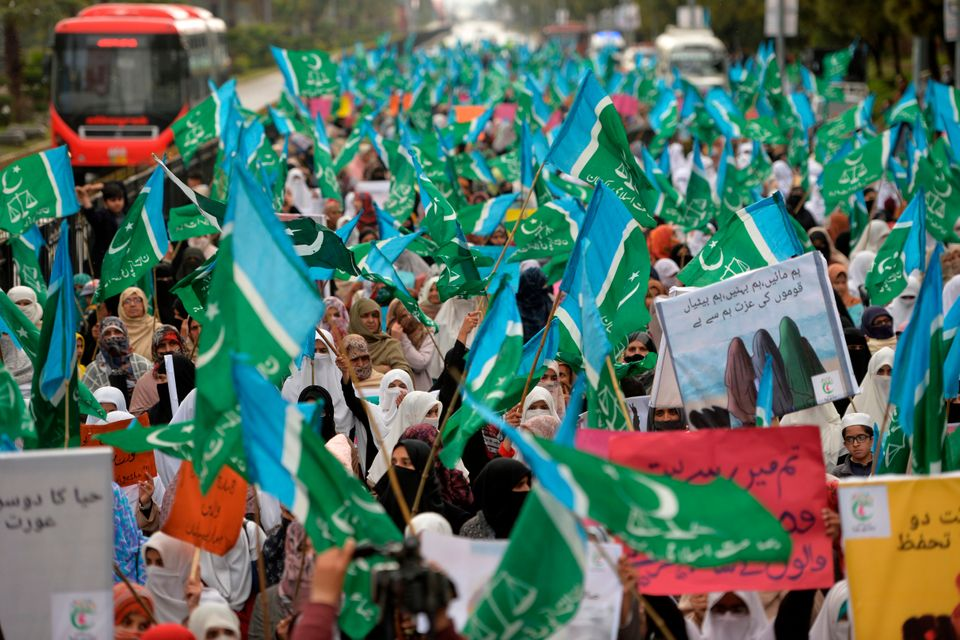 Veiled female supporters of Pakistani Islamic political party Jamaat-e-Islami (JI) carry placards and...