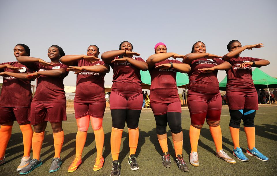 Women line up with their hands arranged as equality signs during a friendly football match in Abuja,