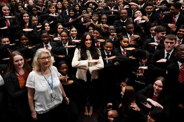 """Meghan poses with schoolchildren making the """"equality"""" sign following a school assembly during a visit to Robert Clack School"""