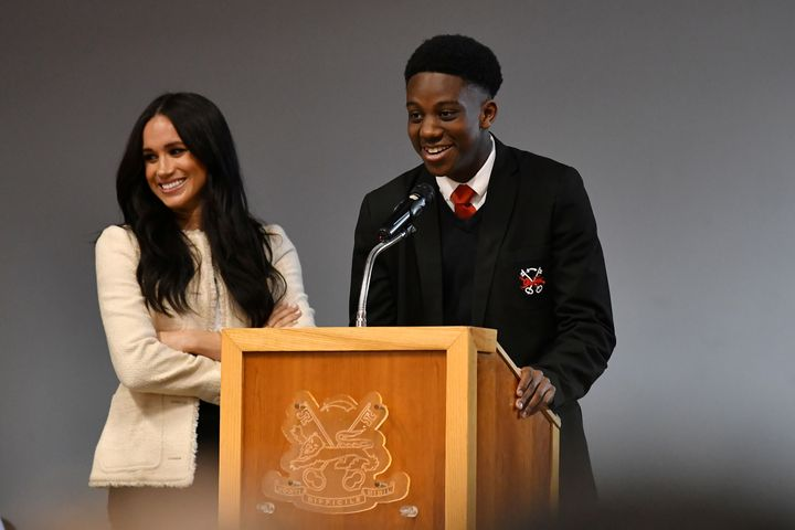 The Duchess of Sussex smiles as student Aker Okoye speaks during a school assembly.