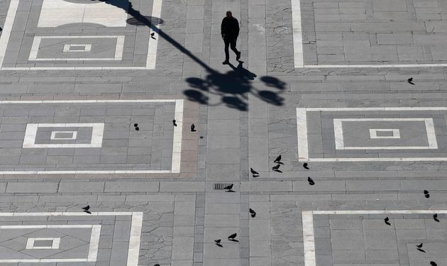 A man walks in Duomo square in Milan, Italy on