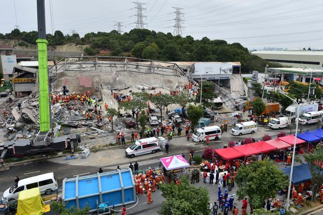 In this photo released by Xinhua News Agency, rescuers search for victims at the site of a hotel collapse...
