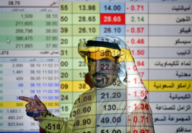 File photo of a trader talks to others in front of a screen displaying Saudi stock market values at the...