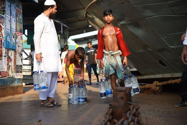 乗船客に飲料水を売りにでかける少年(バングラデシュ)