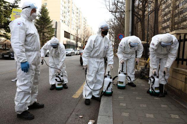 Des soldats sud-coréens désinfectent une rue face au coronavirus à Séoul,...
