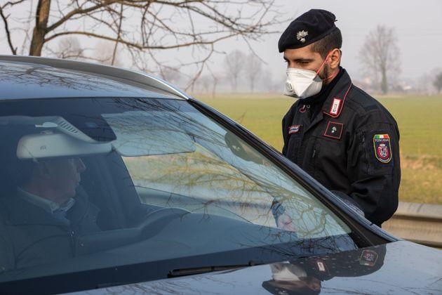 FOMBIO, ITALY - FEBRUARY 24: An Italian Carabinieri officer, wearing a respiratory mask, stops and checks...