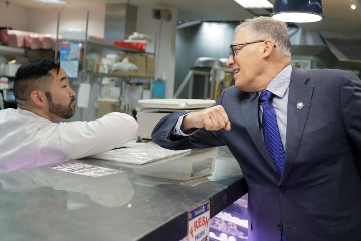 Washington Gov. Jay Inslee, right, bumps elbows with a worker at a seafood counter in Seattle on March 3. Inslee said he's do