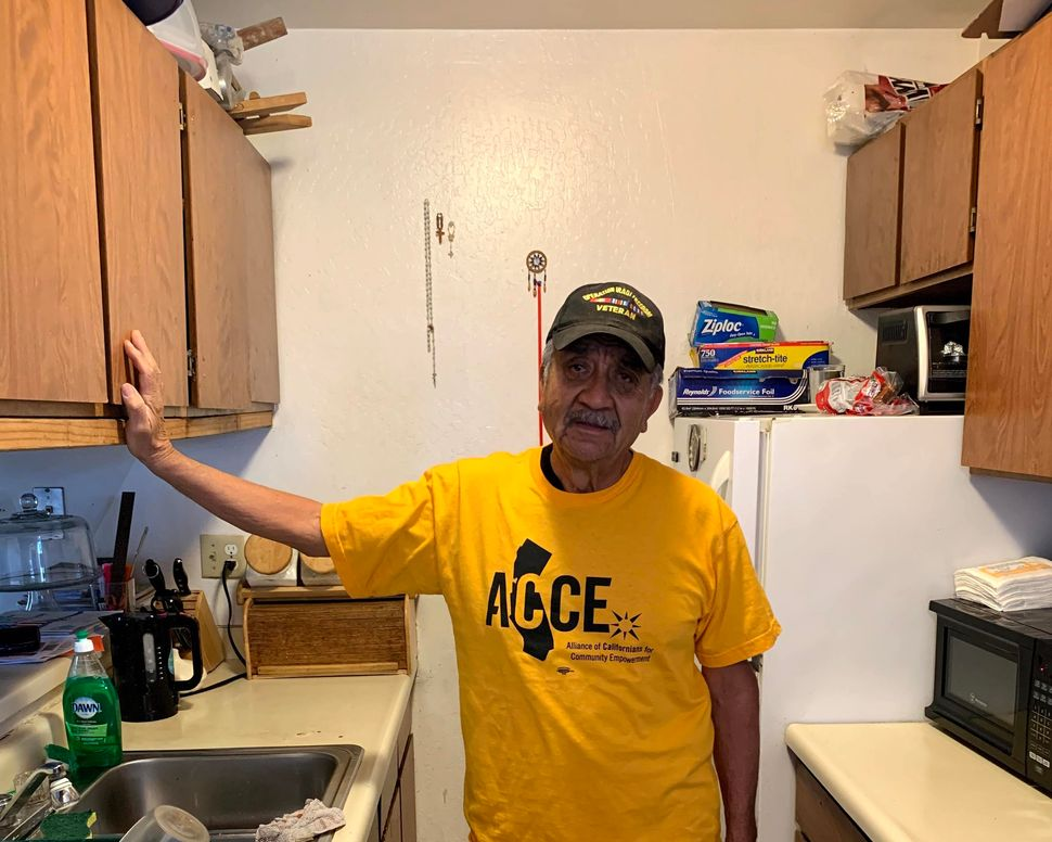 Francisco Perez stands in the kitchen of his Oakland apartment. He is on rent strike to protest the poor conditions of his ho
