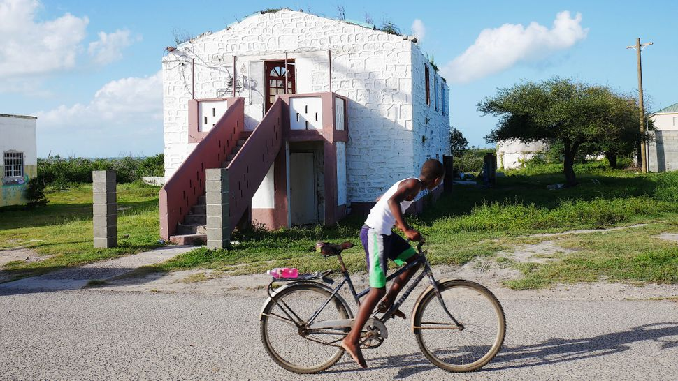 A young boy rides his bicycle past the damaged Barbuda Council Hall in the village of Codrington. Hurricane Irma destroyed 95