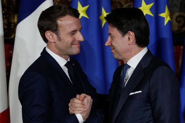 Italian Premier Giuseppe Conte and French President Emmanuel Macron, left, greet each other after a press...