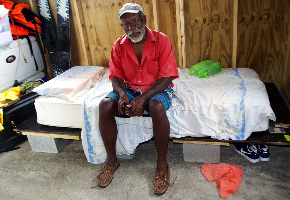 George Jeffery sits in the one-room wooden cottage he just finished building with the help of friends and some supplies given