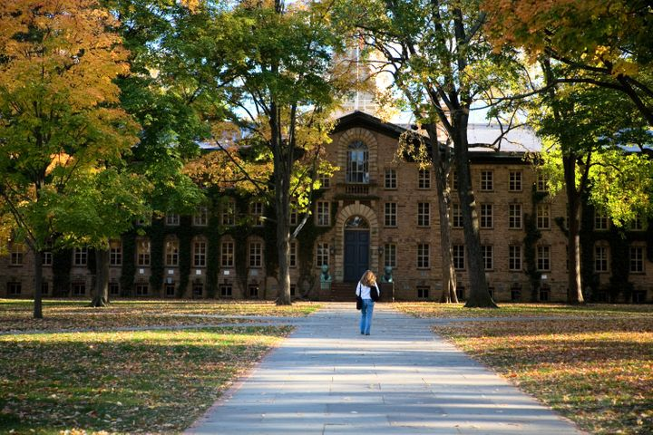 """A student walks toward Princeton University's Nassau Hall. The college plans to begin """"virtual instruction"""" starting March 23"""